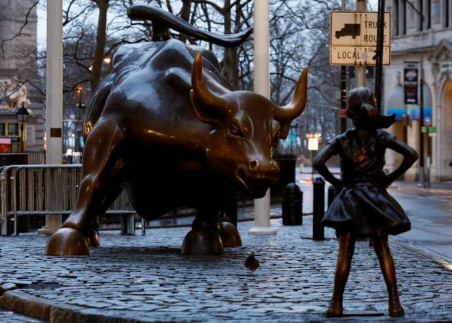 A statue of a girl facing the Wall St. Bull is seen, as part of a campaign by U.S. fund manager State Street to push companies to put women on their boards, in the financial district in New York, U.S., March 7, 2017. REUTERS/Brendan McDermid