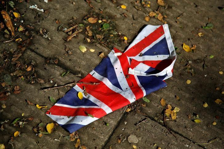 A British flag which was washed away by heavy rains the day before the Brexit vote lies on the street in London, Britain, June 24, 2016. REUTERS/Reinhard Krause