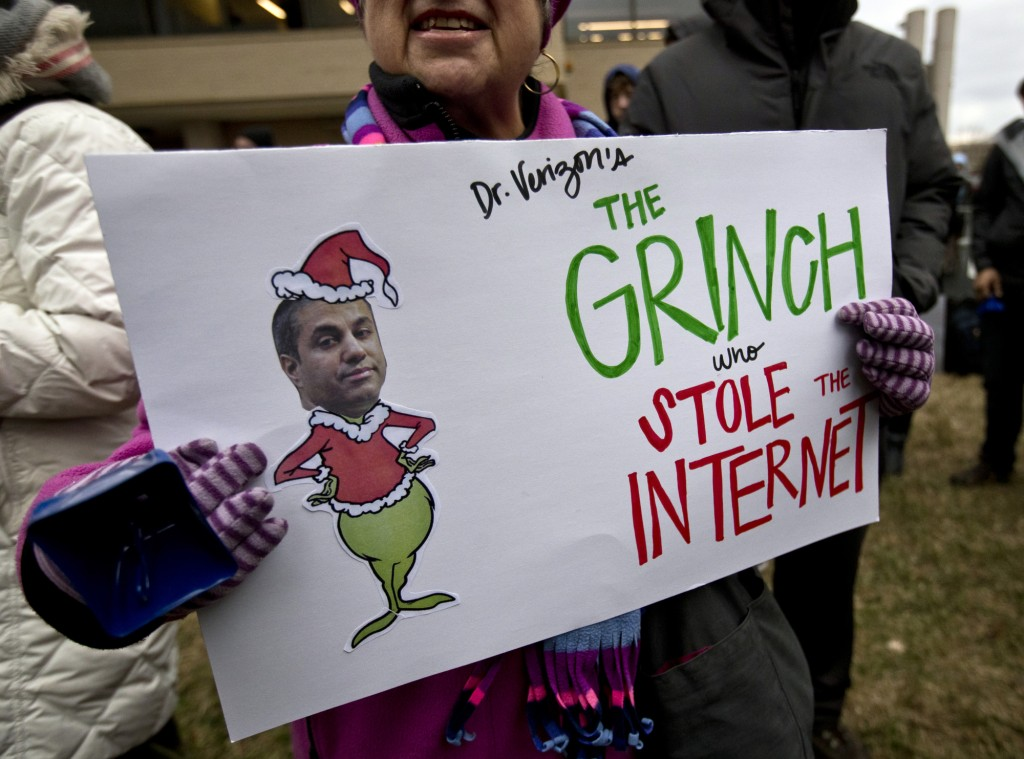 """Diane Tepfer holds a sign with an image of Federal Communications Commission (FCC) Chairman Ajit Pai as the """"Grinch who Stole the Internet"""" as she protests near the FCC, in Washington, Thursday, Dec. 14, 2017, where the FCC is scheduled to meet and vote on net neutrality. The vote scheduled today at the FCC, could usher in big changes in how Americans use the internet, a radical departure from more than a decade of federal oversight. (AP Photo/Carolyn Kaster)"""