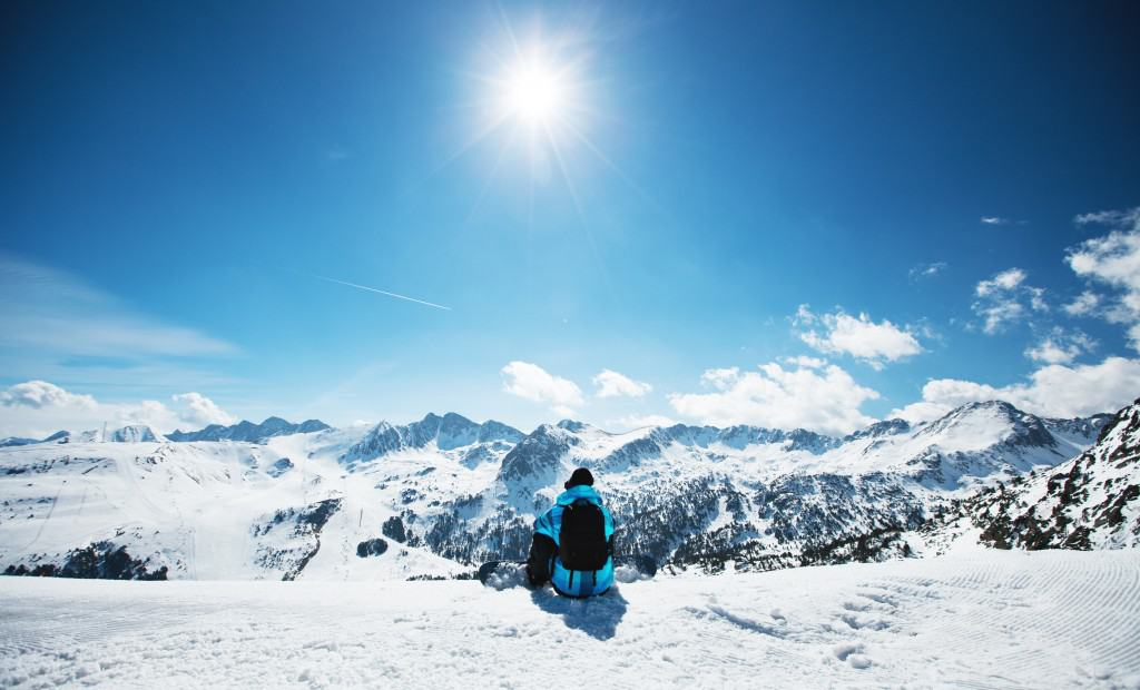 Snowboarder sitting on the edge of the mountain and enjoy the winter landscape. Canillo ski region. Andorra