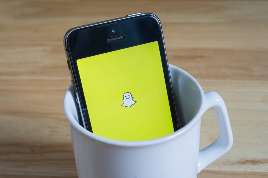 Bangkok, Thailand - April 22, 2017 : Apple iPhone5s in a mug showing its screen with Snapchat logo.