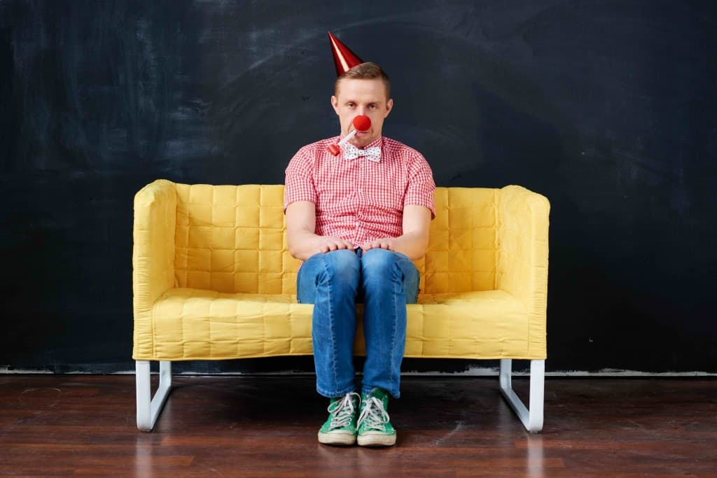 Upset young man with party blower sitting on the sofa