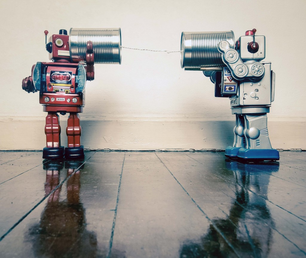 Two retro Robots toys talking on tin can phones on an old wooden floor