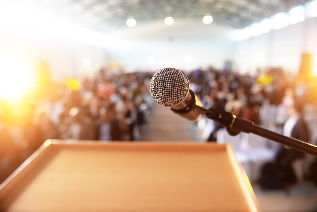 A waiting crowd in front of a microphone and podium