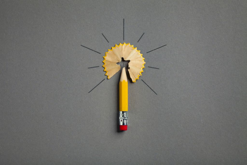 Photography of a pencil on gray paper arranged to a light bulb.