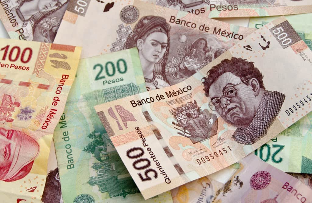 Mexican Pesos, bank notes, colorful background with diferent denominations including 500 pesos currency bills with Diego Rivera and Frida Kahlo faces.